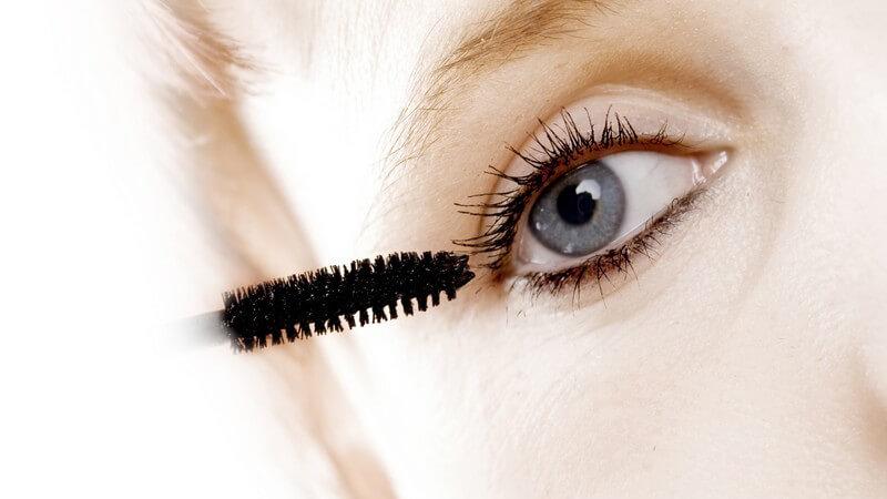 Nahaufnahme blonde Frau mit blauen Augen beim Schminken mit Mascara oder Wimperntusche