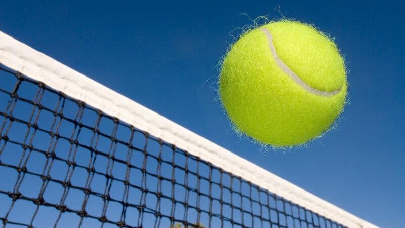 Nahaufnahme Tennisball fliegt übers Netz