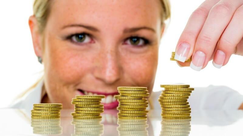 Sparen - Frau legt Geldmünzen aufeinander