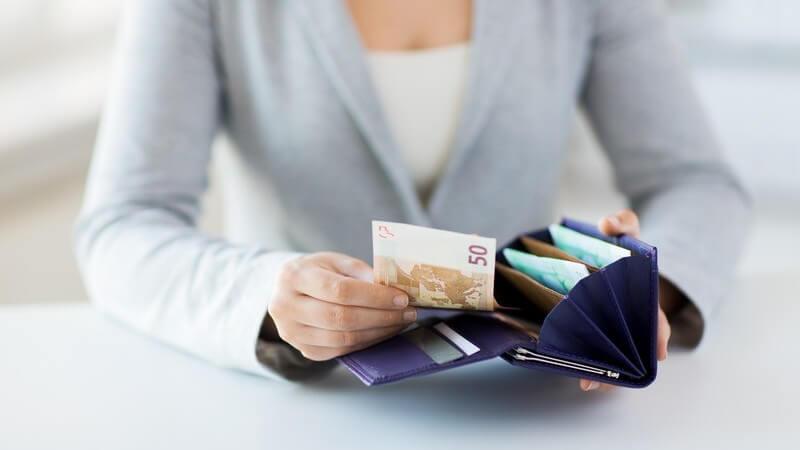 Frau in grauer Strickjacke sitzt am Tisch und nimmt einen 50-Euro-Schein aus der Geldbörse