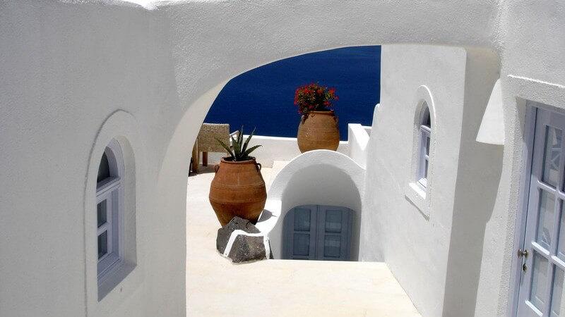 Archipel in Griechenland, kalkweiße Hauswand mit Blumenvasen und Amphoren, im Hintergrund Meer