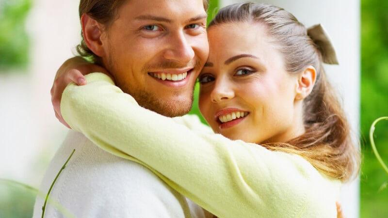 Junges Paar umarmt sich auf Balkon, beide lächeln in Kamera