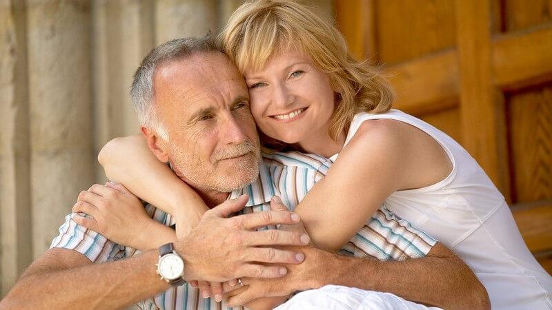 Reifes Paar, sie umarmt ihn von der Seite, Altersunterschied