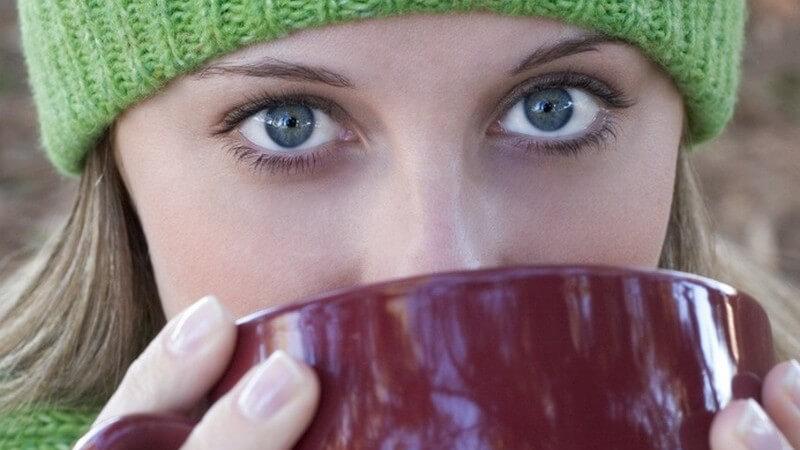 Nahaufnahme von junger Frau mit grüner Wollmütze und blauen Augen, die aus bordeauxfarbener Kaffeetasse trinkt