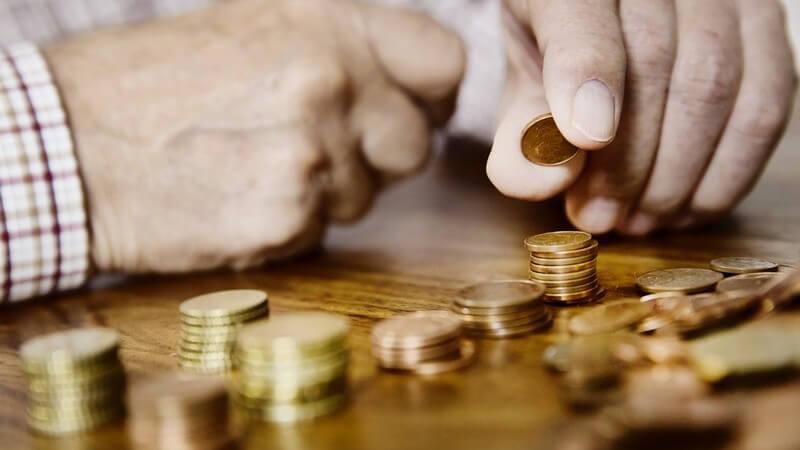 Alter Mann sortiert und zählt sein Kleingeld (Euro-Cent-Stücke) auf einem Tisch