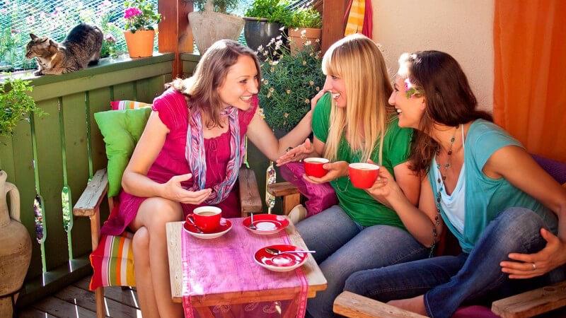 Drei Frauen sitzen auf buntem Balkon und trinken Kaffee aus roten Tassen