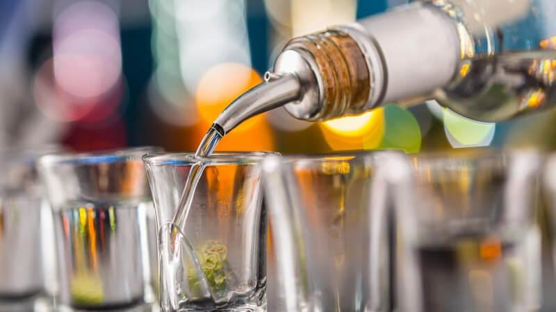 Eine Reihe von Schnapsgläsern wird an einer Bar mit klarem Schnaps befüllt