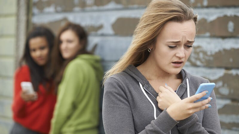 Jugendliches Mädchen liest eine Textnachricht auf ihrem Smartphone, im Hintergrund stehen zwei weitere Mädchen mit Handy