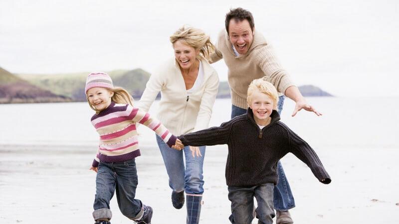Junge Familie hält sich an den Händen und rennt lachend am Strand entlang