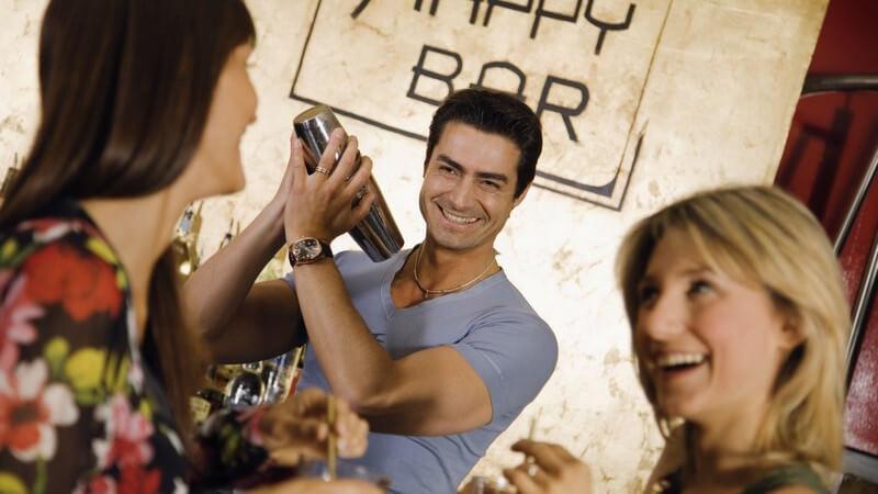 Zwei Freundinnen in Cocktailbar, Mann schüttelt Zutaten für Cocktail, alle lachen