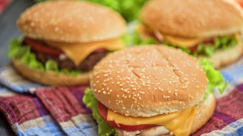 Drei selbstgemachte Cheeseburger auf einem Küchenhandtuch