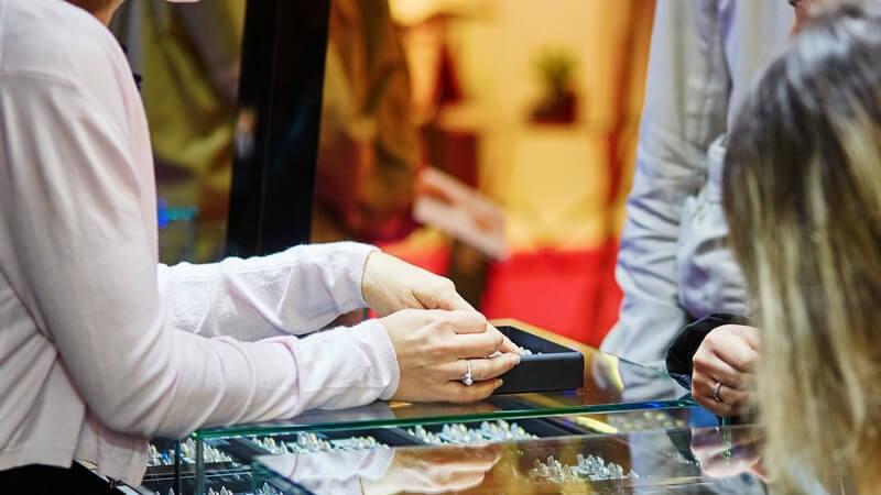 Schmuckverkäuferin berät einen Kunden bei der Auswahl eines Ringes im Juweliergeschäft
