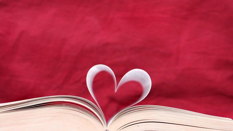 Aufgeschlagenes Buch, Seiten in Herzform, roter Hintergrund