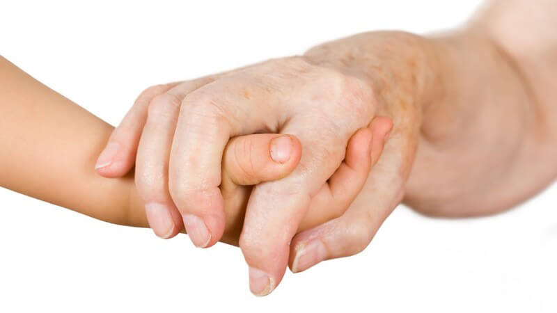 Nahaufnahme zweier sich haltender Hände, kleines Kind und alte Frau