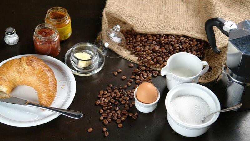 Frühstückstisch mit Kaffee, Zucker, Croissant, Marmelade, Ei und Kaffeebohnen