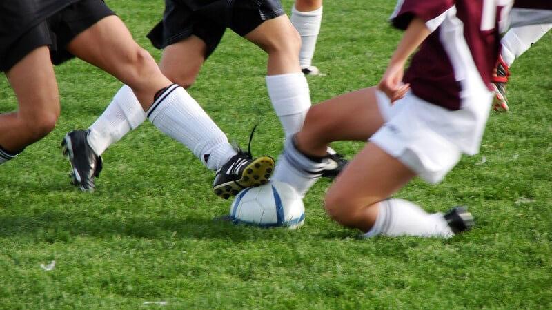 Ausschnitt Frauenbeine beim Fußballspiel auf Rasen