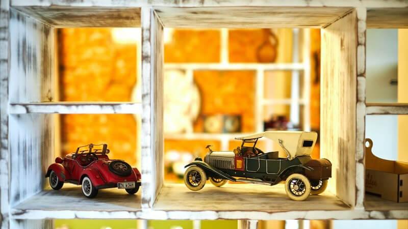 Zwei Oldtimer-Spielzeugautos stehen in einem alten Vintage-Regal