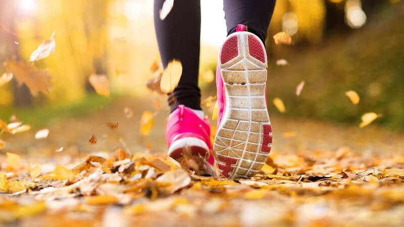 Joggen im Herbst - Laufschuhe auf Waldweg mit Herbstlaub
