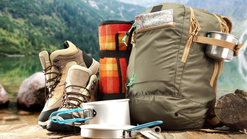 Wanderrucksack, Wanderschuhe und Campinggeschirr auf Holztisch vor Bergkulisse