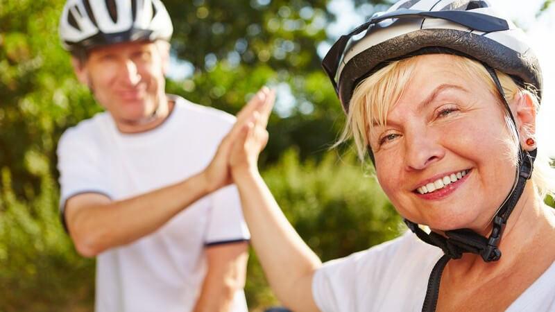 Älteres Paar in Fahrradkleidung und Helm schlägt sich zufrieden in die Hände