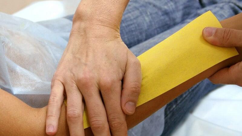 Frau bekommt Wachsstreifen auf Unterarm zur Haarentfernung