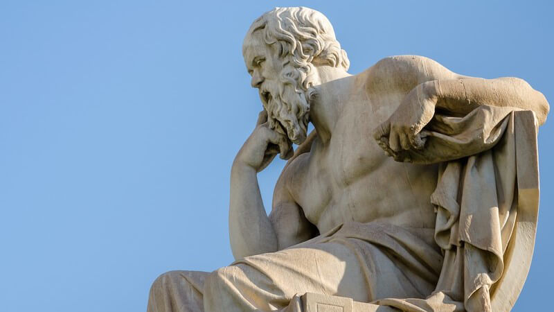 Statue des sitzenden Philosophen Sokrates vor blauem Himmel