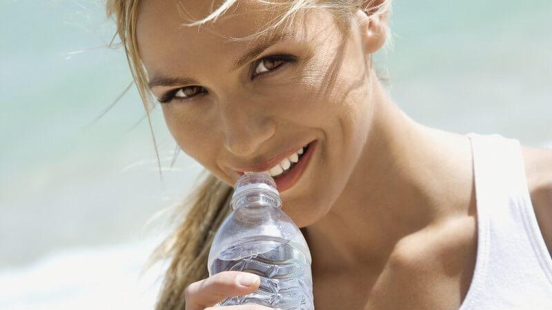 Blonde Frau in weißem T-Shirt trinkt am Strand aus einer Wasserflasche