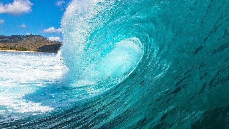 Seitliche Aufnahme, Welle im türkisen Meer kommt aufs Land zu