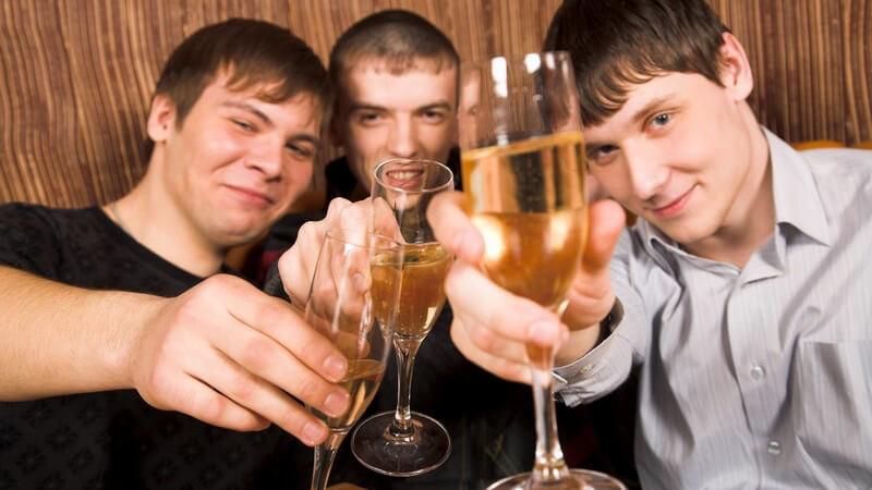 3 Jungs stoßen mit Sektgläsern in die Kamera an