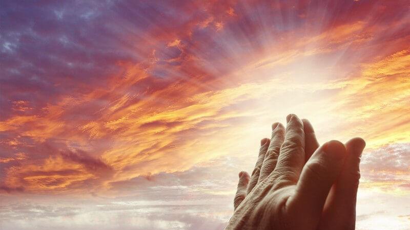 Zum Beten gefaltete Hände unter rötlichem Himmel und Sonnenstrahlen