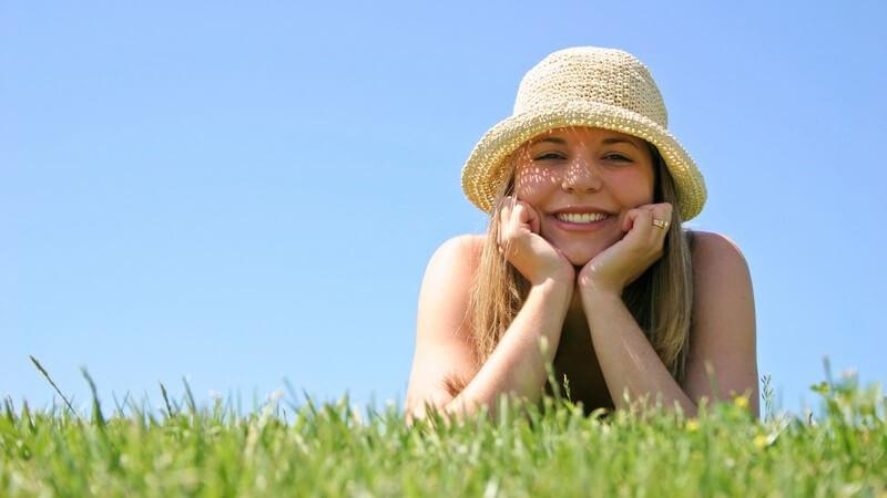 Mädchen mit Strohhut liegt lächelnd auf einer Wiese, den Kopf in die Hände gelegt