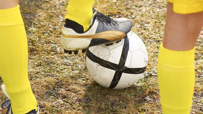 Beine von Fußballern in gelben Trikots mit Fußball