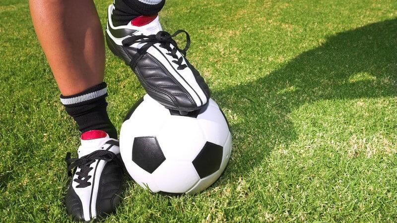Füße eines Fußballers auf Wiese, ein Fuß auf Ball gestützt