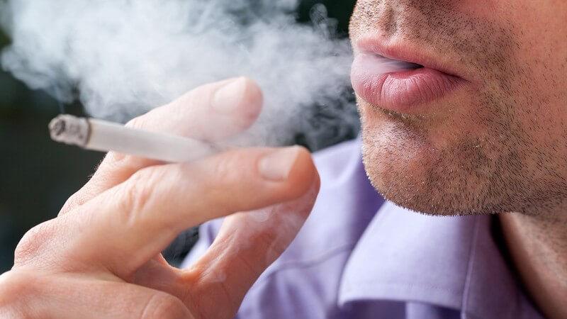 Mann beim Rauchen - er bläst Rauch einer Zigarette aus
