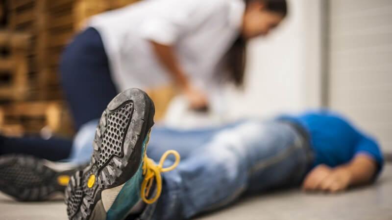 Mann in blauem Poloshirt liegt ohnmächtig auf dem Boden, eine Frau beugt sich über ihn, unscharfe Szene
