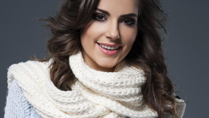 Hübsches Model mit weißem Schal über hellblauem Strickpullover