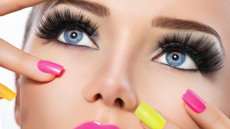 Geschminktes Modelgesicht mit pinkem Lippenstift und pinken und gelben Fingernägeln
