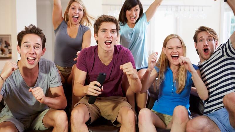 Sechs jugendliche Freunde sitzen mit Popcorn vor dem Fernseher und jubeln