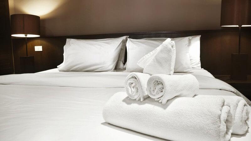 Doppelbett im Doppezimmer eines Hotels, darauf zusammengerollte Handtücher