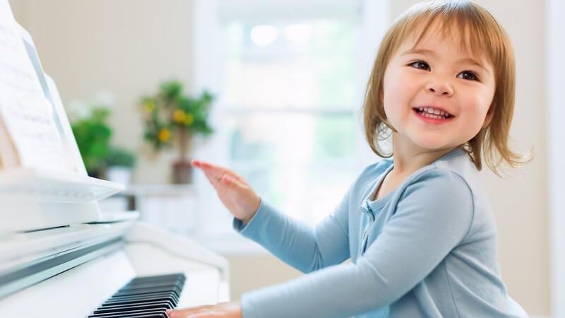 Kleines Mädchen in hellblauer Strickjacke spielt auf einem Klavier