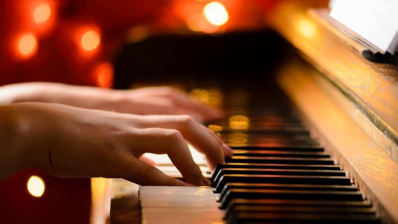 Hände spielen auf einem Klavier, Lichter im Hintergrund
