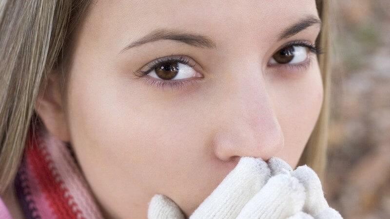 Winter - Junge Frau friert und pustet in ihre weißen Handschuhe