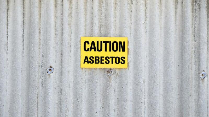 """Gelbes Schild mit Aufschrift """"Achtung, Asbest"""" auf Blechwand"""