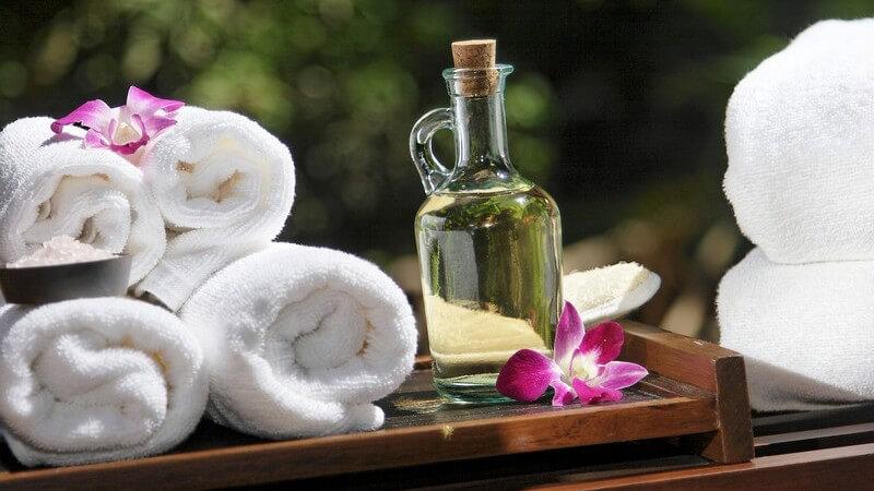 Glasflasche mit Massageöl, daneben vier zusammengerollte Handtücher auf Holztablett