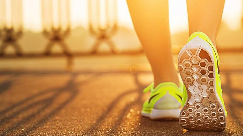 Läuferbeine mit neongelben Schuhen auf Asphalt, starke Sonneneinstrahlung