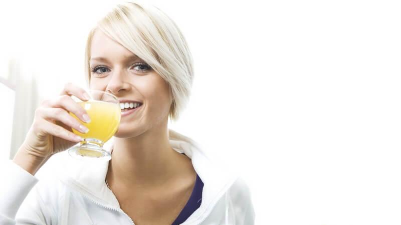 Junge blonde Frau trinkt Fruchtsaftgetränk, neben ihr liegen helle Trauben