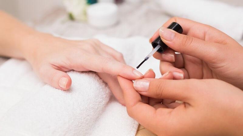 Nageldesignerin trägt einen Nagellack auf den Zeigefinger einer Kundin auf