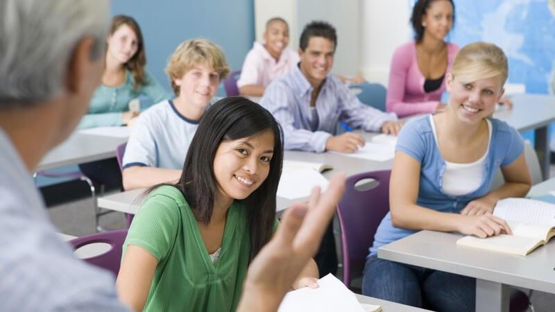 Lehrer steht vor seiner Schulklasse in Klassenraum, Schüler lächeln ihn an