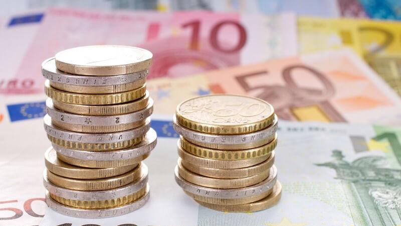 Zwei Stapel mit Euro-Münzen auf Euro-Geldscheinen