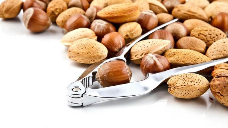 Verschiedene Nüsse mit Nussknacker auf weißem Hintergrund